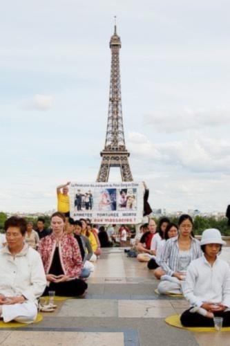 Các đệ tử Pháp Luân Công tập thiền định dưới bóng mát của thápEiffel, Paris rất thanh bình đối lập vớisự đàn áp đang sảy ra ở Trung Quốc.