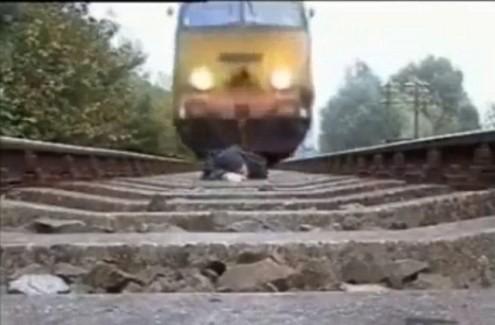 Nằm trên đường ray cho tàu hỏa chạy qua để… biểu diễn