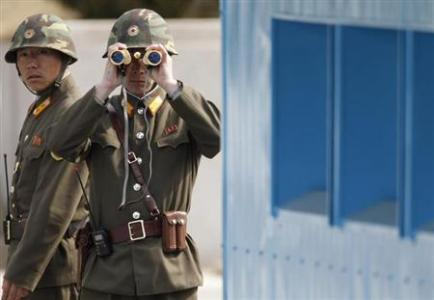 North Korean soldiers look to the South as they patrol at Panmunjom