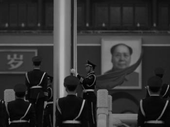 Một sĩ quan cảnh sát bán quân sự nhặt lá cờ Trung Quốc ở phía trước của bức chân dung của Mao Trạch Đông tại Quảng trường Thiên An Môn ở Bắc Kinh vào ngày 02 tháng Ba. Đài truyền hình Trung ương Trung Quốc mới đây trích dẫn lời Mao nói rằng ông sẵn sàng nghe tin hàng trăm triệu người Trung Hoa bị giết. (Feng Li / Getty Images)