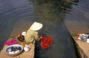 Một phụ nữ Việt Nam giặt quần áo bên dòng sông Mekong AFP photo