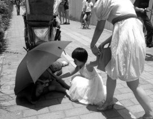 Một bé gái che dù cho một người quét dọn đường phố bị trúng gió bất tỉnh? - Bạn đã bị lừa rồi!