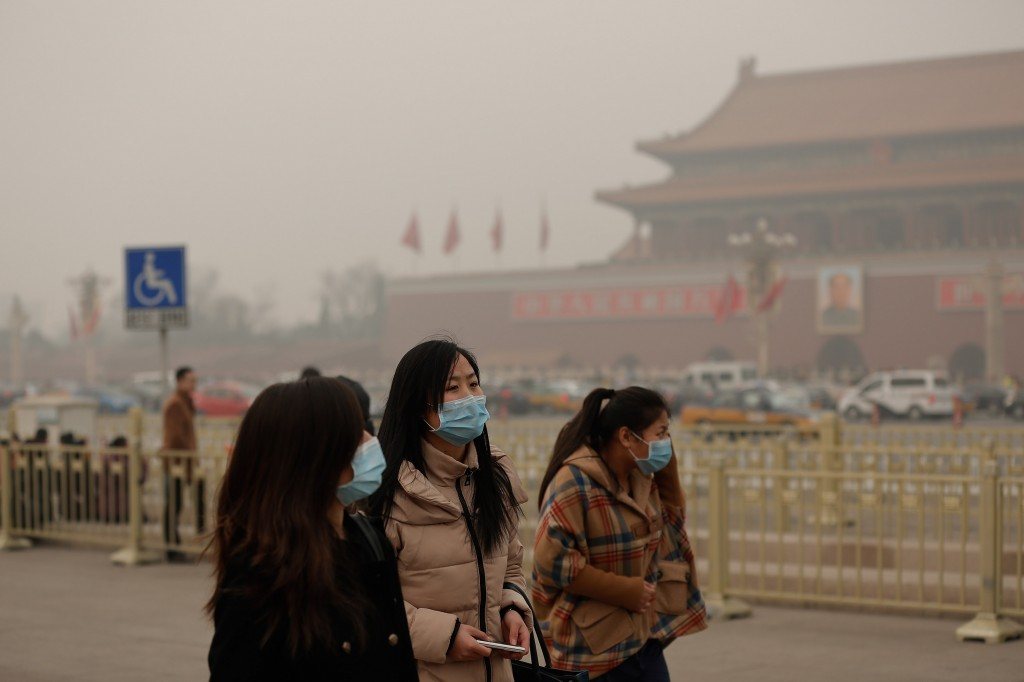 Người dân đi bộ trên Quảng trường Thiên An Môn phải đeo khẩu trang trong suốt đợt ô nhiễm – ảnh chụp vào ngày 25 tháng Hai 2014 tại Bắc Kinh. Phòng cấp cứu tiêm truyền và hồi sức tại các bệnh viện đã quá tải với số lượng bệnh nhân nhập viện (Lintao Zhang/Getty Images)