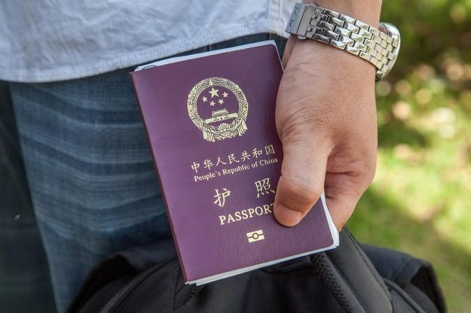 Một công dân Trung Quốc cầm Hộ chiếu Trung Quốc ngày 16/5/2014. Chính quyền đang thắt chặt yêu cầu giấy tờ đi lại của các quan chức Trung Quốc, nhằm ngăn chặn họ trốn chạy khỏi Trung Quốc. (Omar Havana/Getty Images)