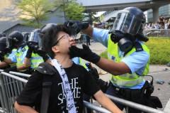 Ngày 29/9, một cảnh sát đứng trước trụ sở chính quyền lấy chai nước của mình và rửa đôi mắt cho người biểu tình vừa bị anh ta xịt hơi cay. Ảnh epochtimes.com