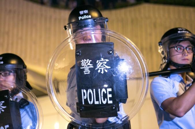 Cuộc đụng độ giữa cảnh sát và những người biểu tình sau khi người biểu tình chặn đường Lung Wo – một trong những tuyến đường chính ở Hồng Kông – vào ngày 15/10/2014. Đêm 15/10, cảnh sát trả đũa bằng việc đánh đập người biểu tình bằng nắm đấm, dùi cui, và hơi cay (Benjamin Chasteen/Epoch Times)