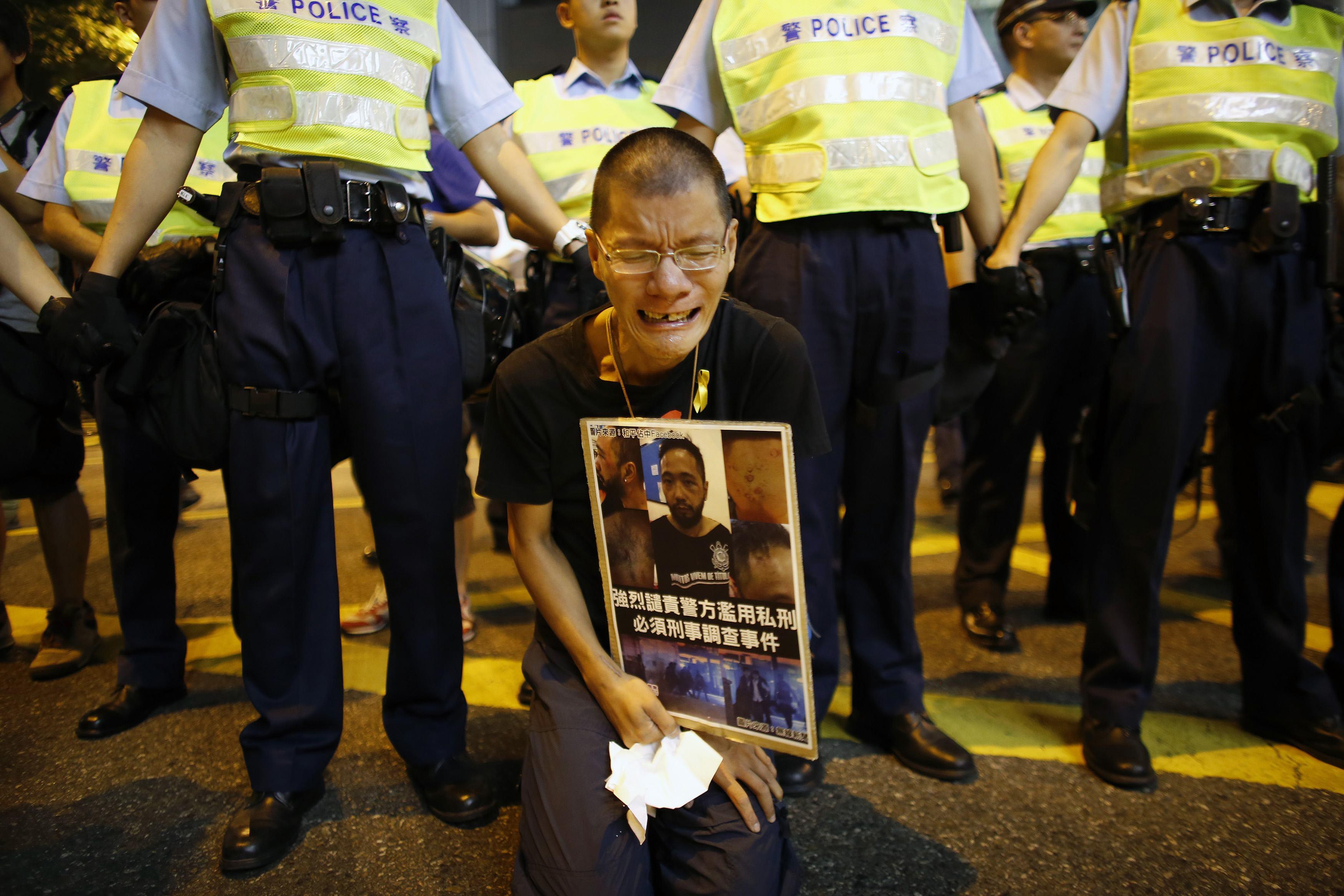 Người đàn ông cầm bức ảnh miêu tả Tằng Giang, thành viên của Đảng Dân sự bị các nhân viên cảnh sát mặc thường phục đánh đập tại khu vực biểu tình chính ở huyện Admiralty, Hồng Kông vào ngày 23/10/2014. Sau cuộc điều tra, 7 nhân viên an ninh tham gia đánh đập đã bị bắt vào hôm 26/11. (Ảnh: Internet)
