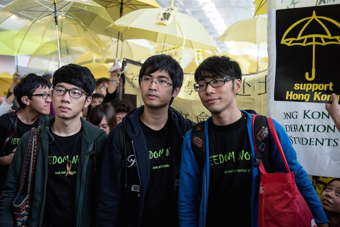 Thủ lĩnh sinh viên Alex Chow (giữa), Nathan Law (trái) và Eason Chung (phải) được người biểu tình ủng hộ dân chủ vây quanh tại sân bay quốc tế Hồng Kông trước chuyến bay theo lịch trình đến Bắc Kinh vào ngày 15/11/2014. (Alex Ogle/AFP/Getty Images)