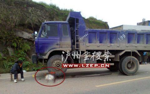 Mẹ của Xiong Maoke ngồi thất thần cạnh thi thể em đang mắc kẹt dưới bánh xe tải (trong vòng tròn đỏ). Ảnh: Lzep.cn