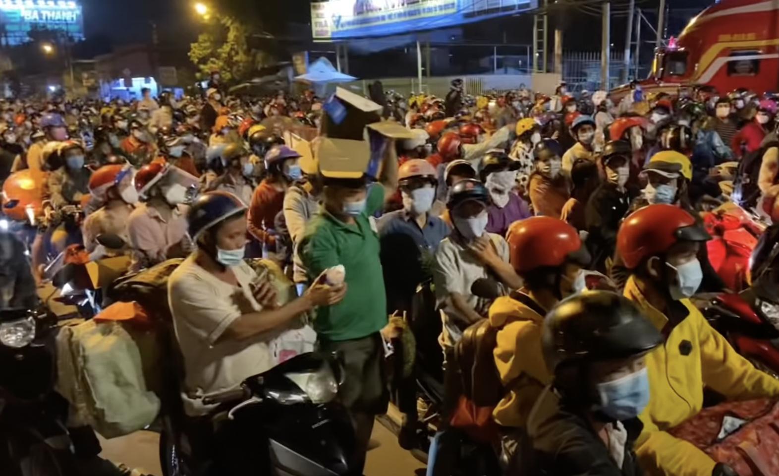 Một người tốt bụng phát nước miễn phí cho người dân về quê nhưng bị chặn lại tại cửa ngõ giáp Long An sau khi TP. HCM nới lỏng giãn cách xã hội và tháo dỡ các chốt kiểm soát liên quận. (Ảnh chụp màn hình Saigon Now)